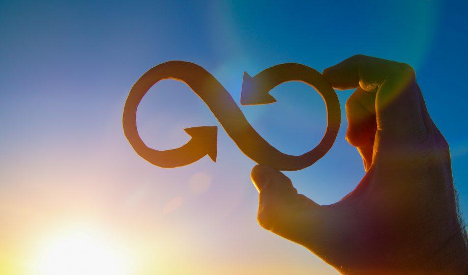 一个人手里拿着无限的象征,面对着天空和耀眼的太阳, 经营理念的想法.