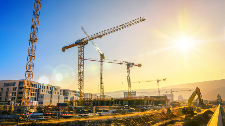 大型建筑工地包括几台起重机,天空晴朗,阳光明媚