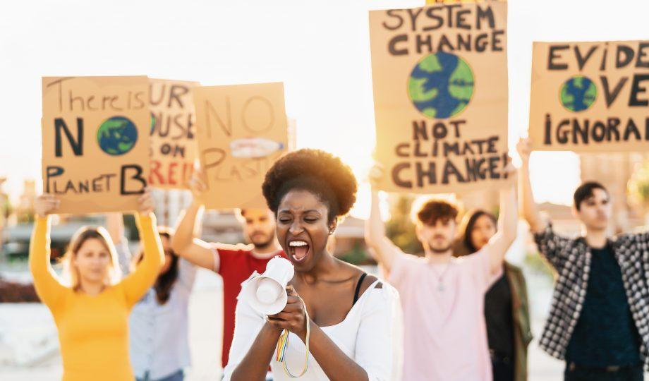 抗议塑料污染和气候变化的团体示威者-多种族的人在道路上举着环境灾难的横幅-全球变暖的概念
