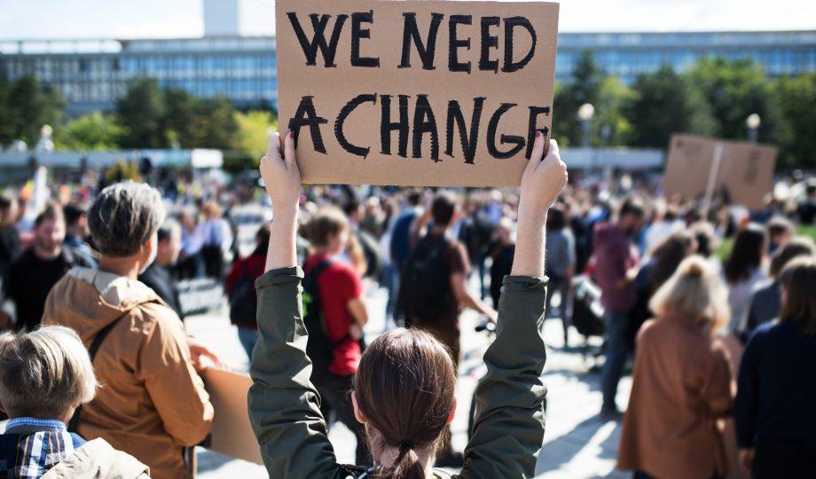 在全球气候变化罢工的海报和海报的人的背面.