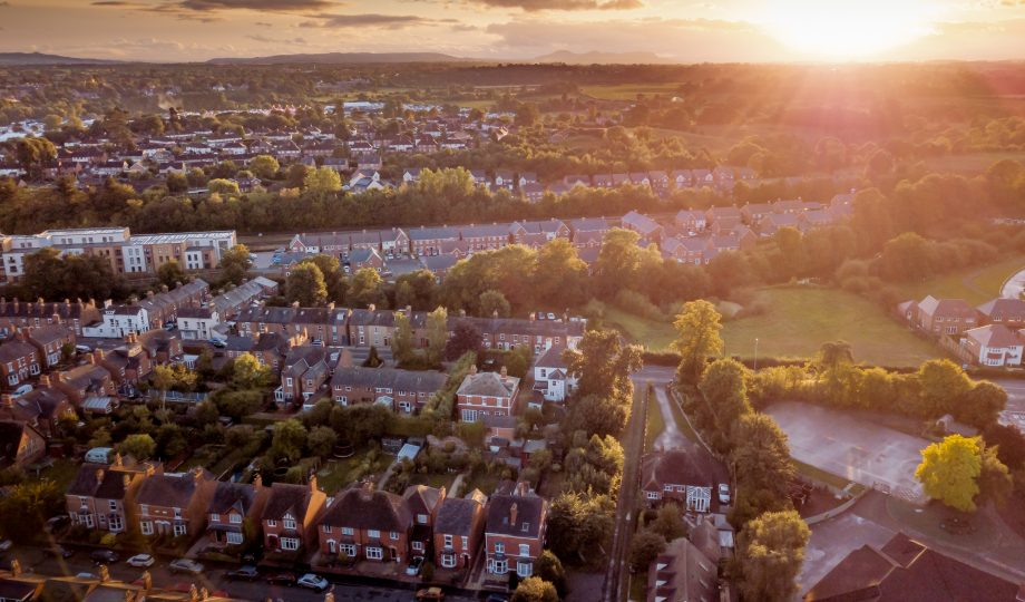 Sun setting with atmospheric effect over traditional British houses and tree lined streets.