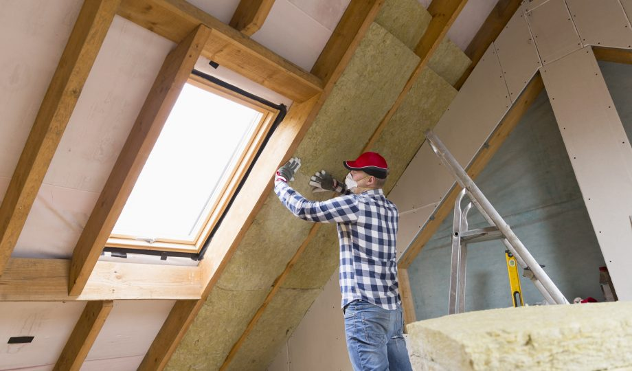 Man installing thermal roof insulation layer – using mineral wool panels. Attic renovation and insulation concept