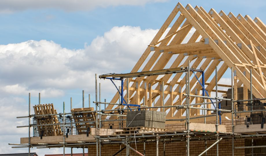 Construction industry. Timber framework of house roof trusses with scaffold.