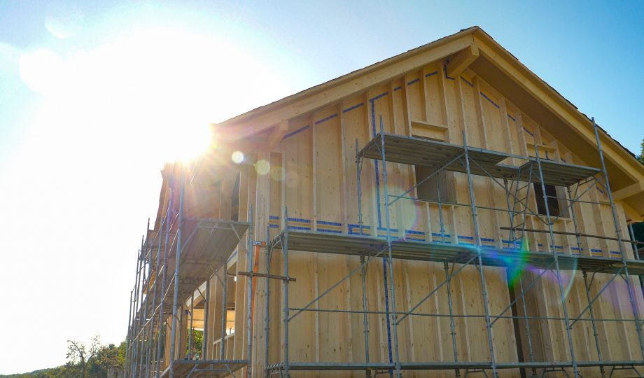 CLOSE UP: Bright sunbeams shine on a wooden house being built in countryside.